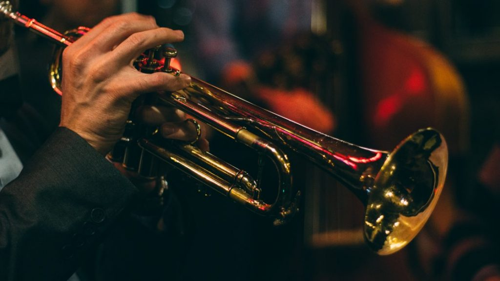 A man's hand on the keys of his trumpet. In the blurred background we can make out a bass.