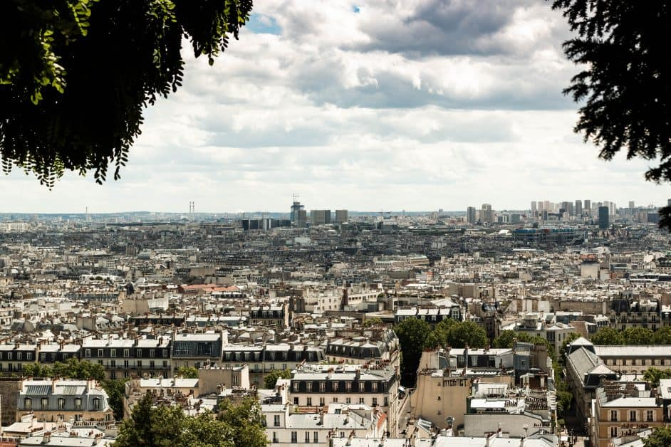 A view of Paris from Montmartre. We see what sems like endless rooftops and a few buildings in the distance, beneath a typically partly cloudy Paris sky.