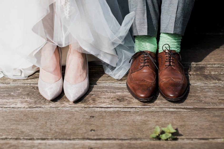 We see a couple that seem to be sitting together, but we can only see from the front of their calves, down. The woman wears a long white skirt or dress and white high heels. The man wears grey slacks, green socks, and brown Oxford shoes. They appear to be a bride and groom.