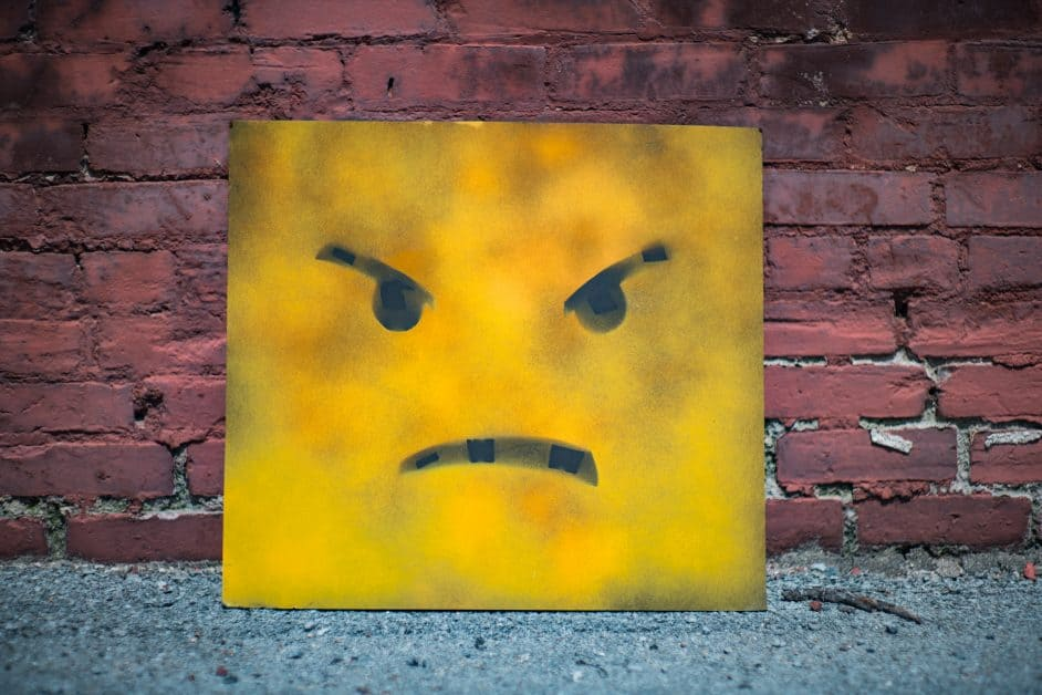 A large yellow-painted cardboard panel leans against a red brick wall. On the panel is painted an angry-looking face in the style of an emoticon. The ground beneath it is gray gavel