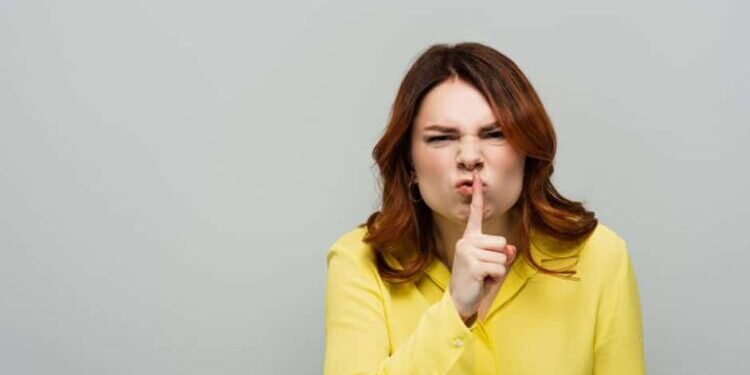 """An angry-looking woman with red hair and a yellow blowse puts a finger to her lips in the classic """"shush"""" gesture"""