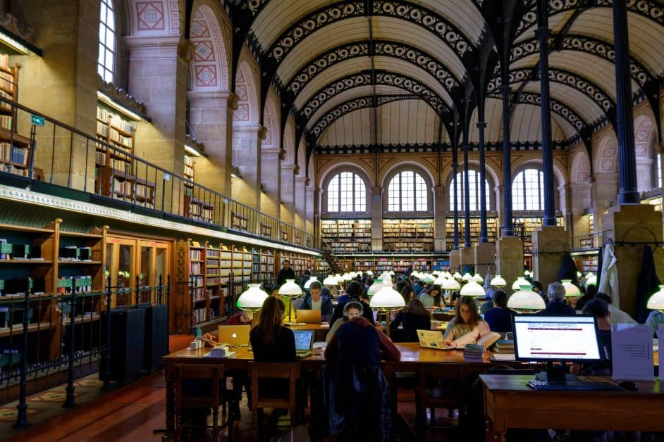 A view of the bibliothèque Sainte-Geneviève in Paris. This library, mostly used by university students, is famous for its vaulted cielings decorated with lace-like metalwork. Below are arched windows and two stories of bookshelves against the walls. In the center of the photo as well as the library itself are lots of work tables with old-fashioned green-lidded lamps next to each seat. Students are seated working on their computers.