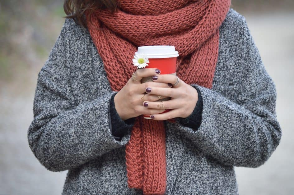A woman holds a takeaway cup of coffee and a daisy in her hands. Her nails are painted an awesome shade of purplish-brown. We see only her torso. She is wearing a comfy gray cardigan and over it a muted orange scarf that looks just perfect for wrapping around your neck and nose to keep warm.