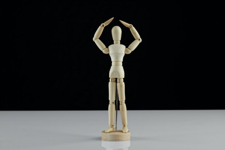 A wooden artist's model is posed with his arms lifted up and his hands meeting over his head. He is on a white surface and in front of a black background.