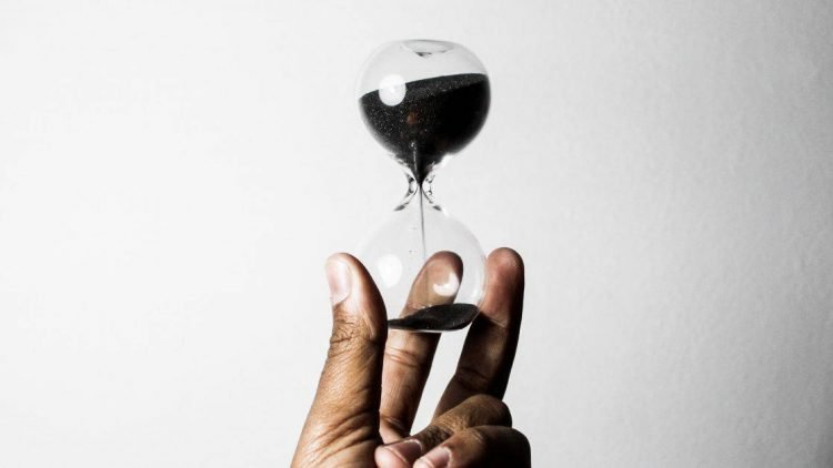 A man's hand holds a small hourglass. The hourglass has no wooden frame and is filled with black sand. Most of it is in the top part of the hourglass, but it is flowing down to the bottom, where some sand has already accumulated. The background of the photo is a gray-ish white wall.