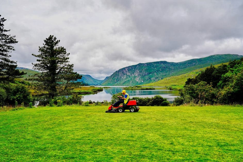 A man in a yellow vest and construction hat sits on a red riding mower in the midst of a lush lawn, pine trees just behind him, and far-off mountains covered in green vegetation as well.