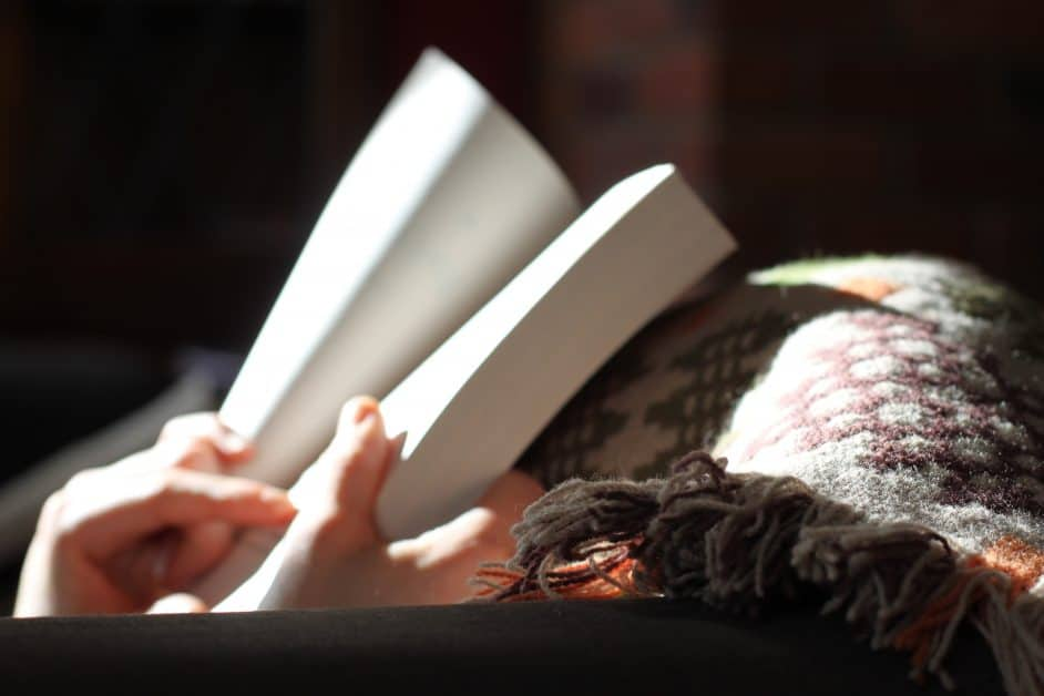 A woman's hands hold open a paperback book to the title page. Her legs are covered in a cozy blanket with a fringed edge.