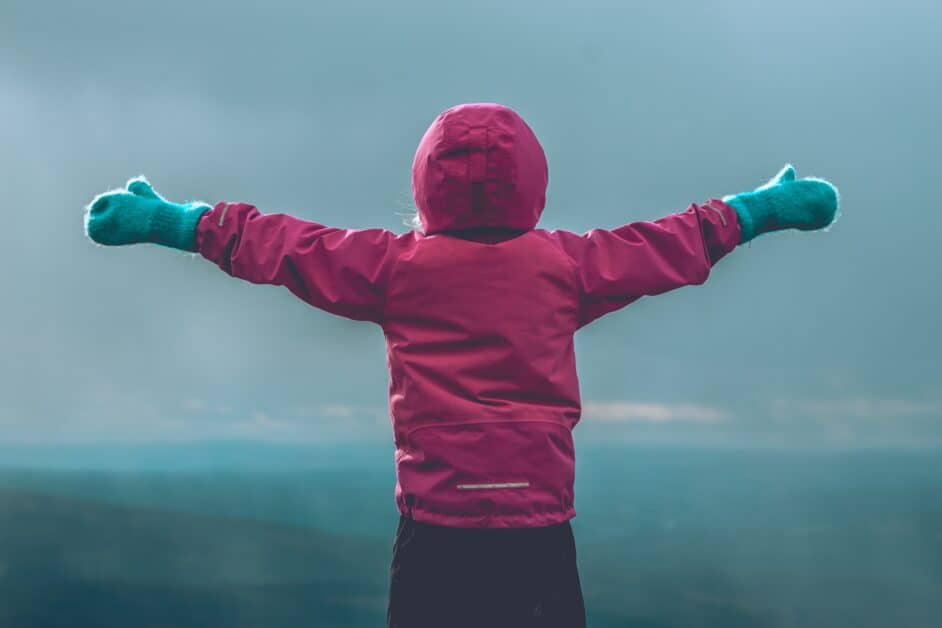 A child in a red hooded coat and green mittens holds their arms wide over a landscape of mountains in the distance.