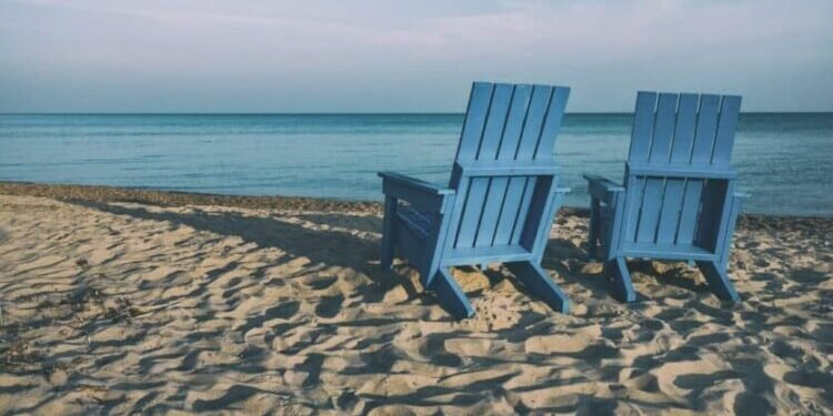 Two blue-painted wooden adirondak chairs face the ocean. They are on a sandy beach, at a slant from the viewer. The weather is sunny, even a bit hazy.