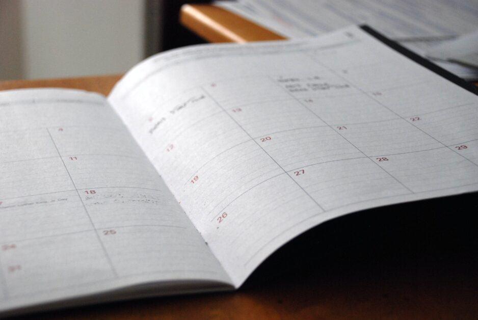 An open calendar planner on a desk.