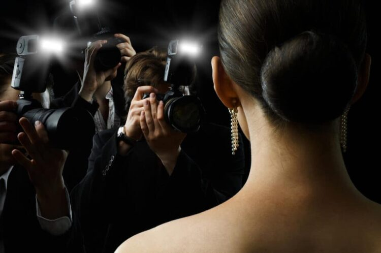 A woman with dangling pearl earrings and her brown hair done up in a stylish, impeccable bun, faces a group of paparrazi