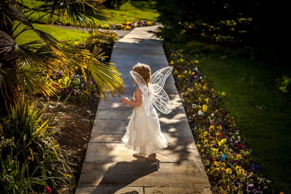 A little girl dressed in a white fairy costume stands on a wooden sidewalk lined with landscaping and flowers.