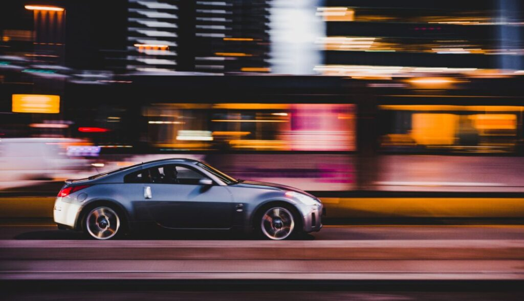 A luxury car speeds past a blurred cityscape. We see the car in profile in the middle ground. It is silver colored.