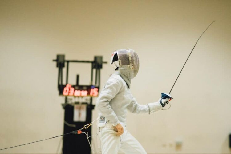 A fencer in profile holds up their foil. This is modern-day competitive fencing so they are attached by a cord behind them and in the background is a scoreboard with red numbers.