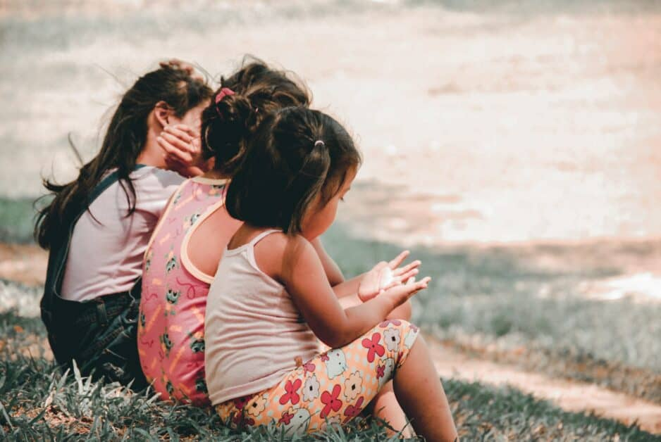 Three little girls in summer clothes sit together outdoors. The photo is taken from the back and slightly to the side so that we see their backs and hair and a very small portion of the first girl's face in profile. She is holding her hands open in front of her as if coutning or telling a story.