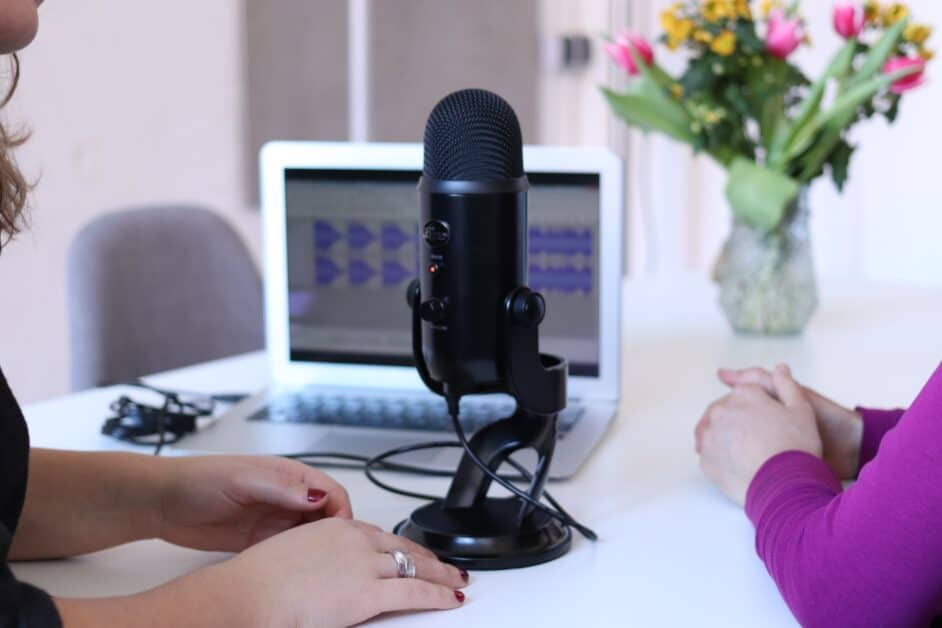 A black professional recording microphone, used for radio or podcast interviews, sits on a white table. In the background is a laptop that shows that soundwaves are being recorded. Behind that appears to be a door or window and on the other side, on the table behind the computer, a bouquet of pink and yellow flowers. In the forgrownd we see the hands of what seem to be two women. One wears long sleeves in a violet color, while the other has dark red painted nails, a silver ring, and a short-sleeved black top or dress. We can see this woman's chin and a bit of her hair, which appears to be slightly wavy, brown, and shoulder-length. The women appear to be speaking together for a podcast or other audio recording.