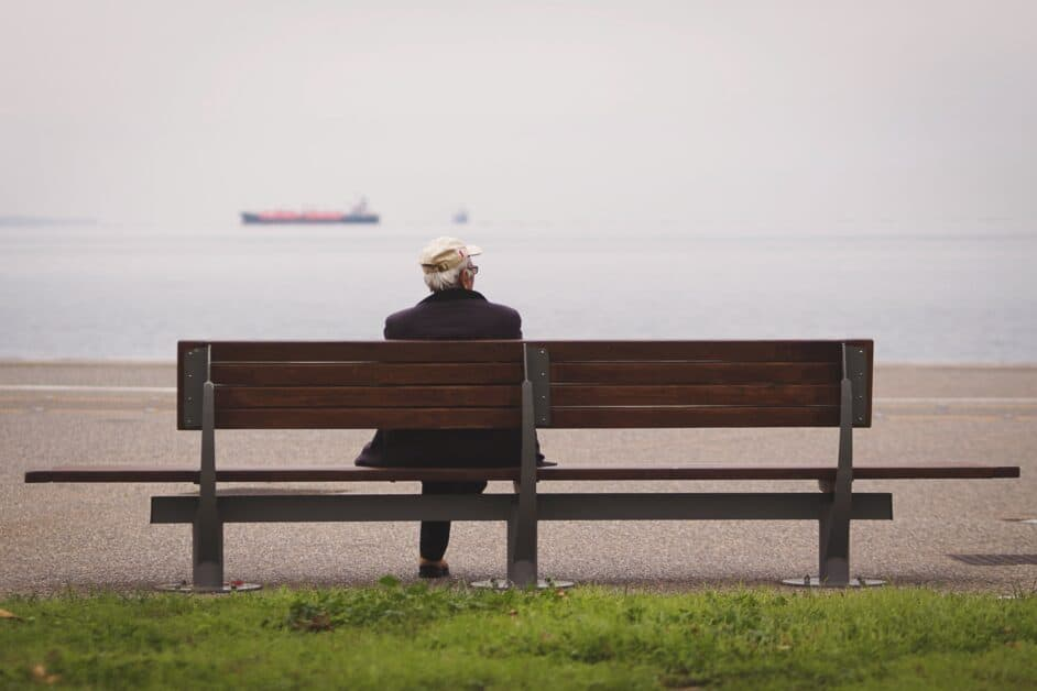 An old man in an off-white baseball cap sits on a bench and looks out at a seascape, where a barge is in the distance.