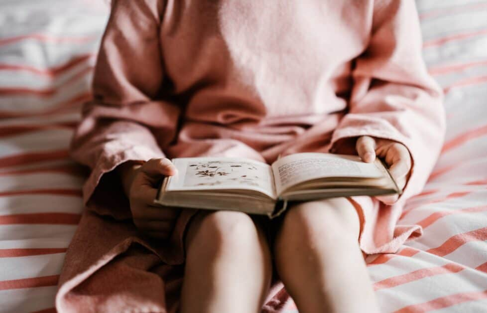 A woman in a loose-fitting pink dress sits on a bed and has an open book in her lap. The book looks like it has writing on one siade and an image of flowers on the others.