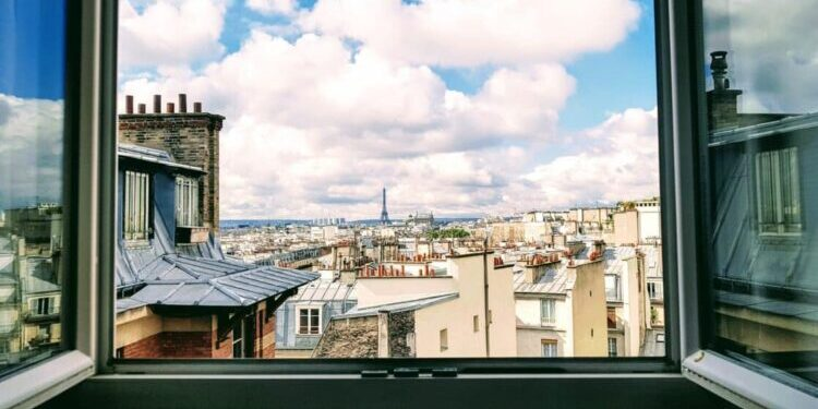 An open window gives out onto a view of Parisian rooftops. We see the Eiffel Tower in the far distance. The day is sunny, with lots of puffy white clouds in the sky.