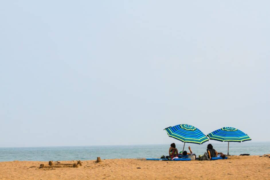 A view of a beach. A group of people lay on beach towels beneath two blue sand black, yellow, and green striped beach umbrellas. A short distance from there, we see a sandcastle. In the background, we see the ocean, which the people under the umbrella are looking towards.