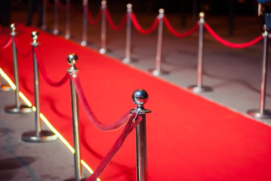 A red carpet at night. The view is from the side, as if the viewer is within the velvet ropes and about to turn a corner to get onto the main strip of red carpet.