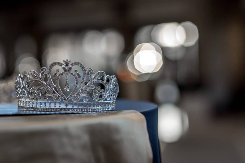 A small, elaborate diamond tiara or crown, with a small teardrop diamond or crystal hanging from the oval sits on a smallish round table that looks partially covered by a satin tablecloth, or maybe that's a dress or decorative cloth or garment. The background is blurred.