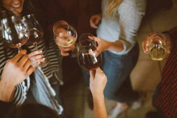 Overhead view of a group of friends standing and drinking wine. Some have white wine and some have red. It looks like they've just clinked their glasses together in a toast. We can see some people's shirts and legs and the lower part of the face of one woman, who is smiling.