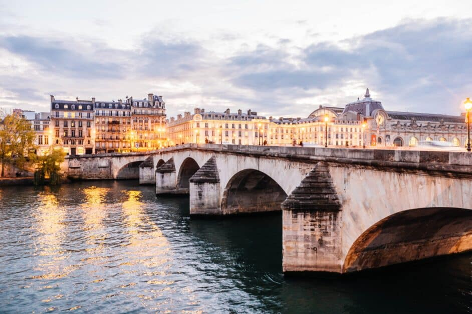 The Pont Royal, a bridge in Paris. We see it from one side of the Seine, looking at the Musee d'Orsay and some typically beautiful Parisian buildings on the other. The sky is partly covered by gray clouds and the streetlamps on the bridge and banks of the Seine are lit already.