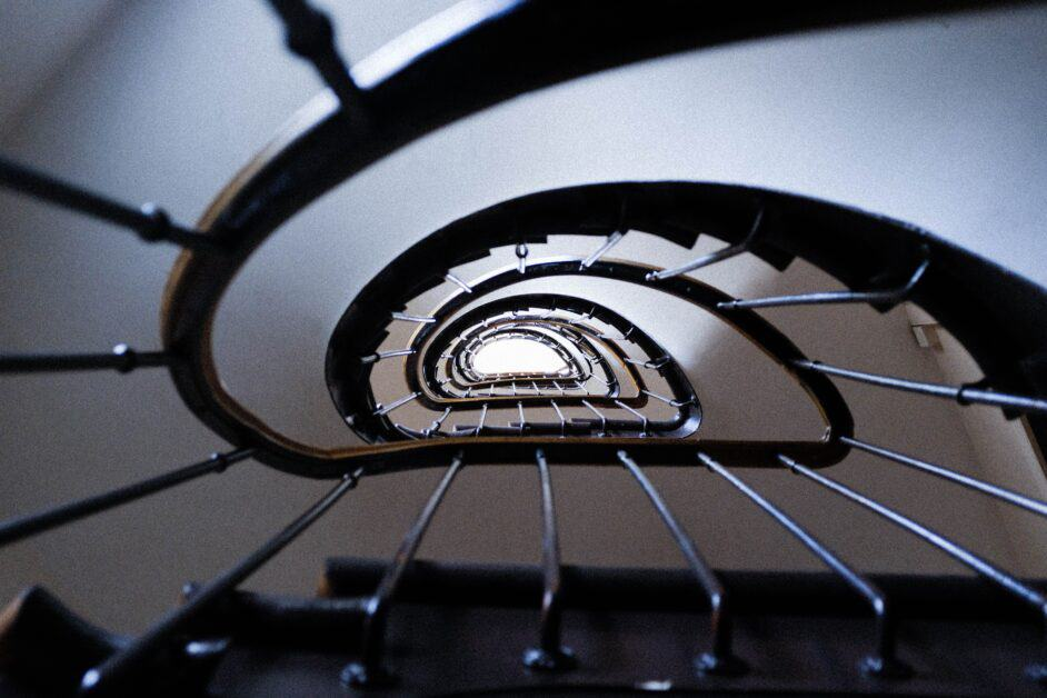 A view looking up in the stairwell of a typical Parisian apartment building. The bannisters are wood, the railings are metal bars, and the shape looks like a slightly warped curve, which is why so many people like to take pictures like this!