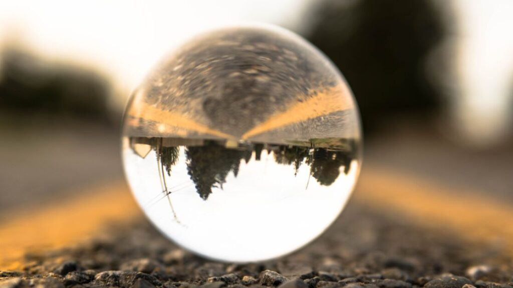 A crystal ball reflects a paved road with yellow lines and the treeline and electric lines above - but upside-down.