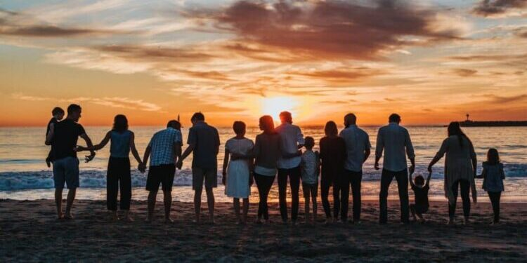 A long line of what seems to be family members, including adults, children, and babies being held in adults' arms, stands on a beach near the water and looks out over the ocean. It's near twilight and the sky is colorful with sunset, light blues and oranges, with a few shadowy, wispy clouds.
