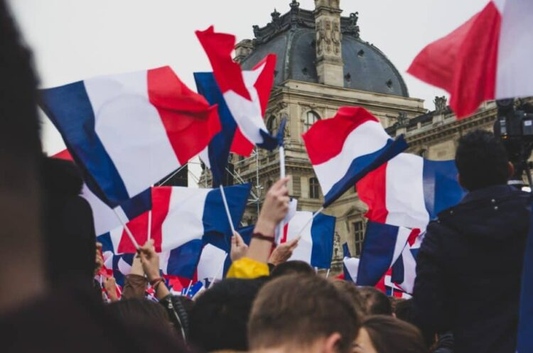 A crowd holds up French flags outside a building possibly the Louvre. In the foreground, a man and woman seem to be kissing but we can only see their foreheads.