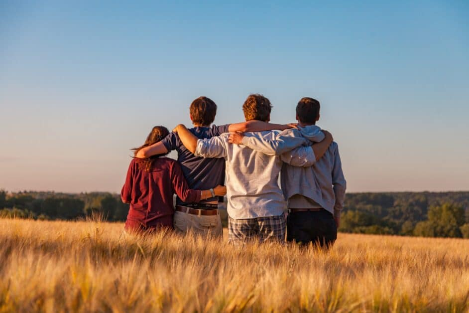 A group of four people, three young men and a young woman, probably in their teens or twenties, link arms and look at the horizon. They are standing in a wheat field. The view is looking down into a forest that extends to the horizon. The weather is sunny.