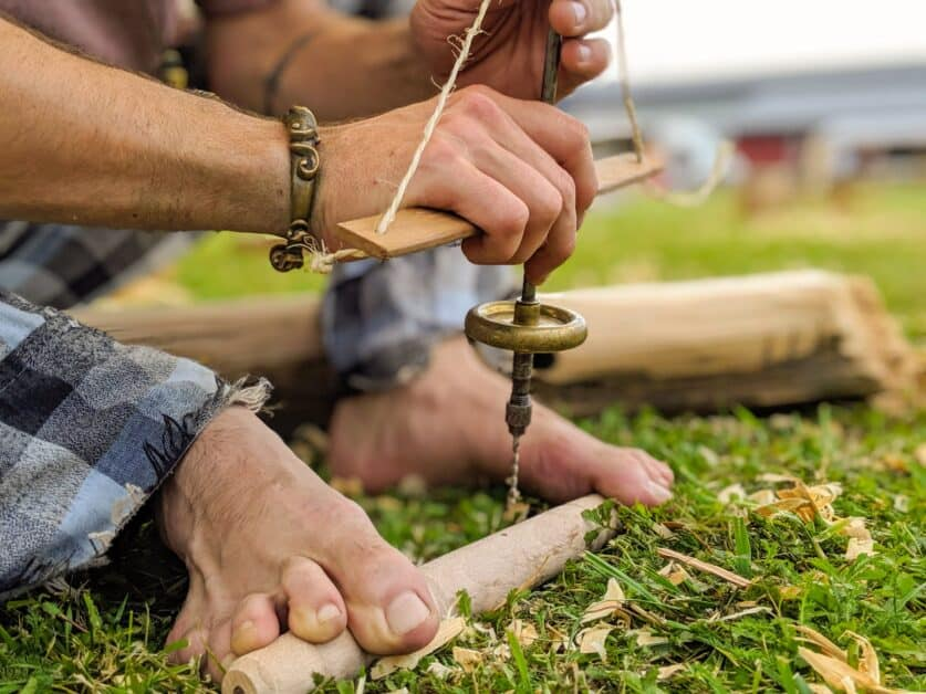 The feet of a historical reenactor dressed as a Gaul in traditional plaid-style trousers, with a gold or bronze bracelet and bare feet is using a tool the make a hole in a wooden cylindrical object, possibly to create some sort of wind instrument.