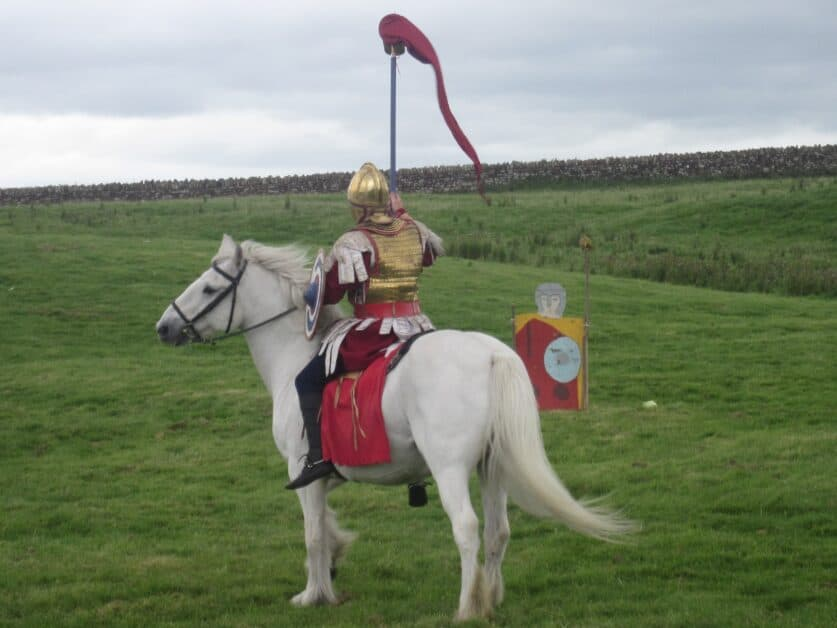 A man dressed as a knight in golden armor, with a small painted wooden shield and riding a white horse, looks out over a field with what appears to be an old stone wall in the distance. He holds a red pennant high in the air.