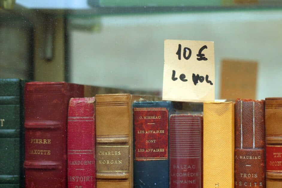 The top of a row of hardcover, leather-bound French books, including a story collection by Mauriac. The ticket shows a price of 10 euros per book.