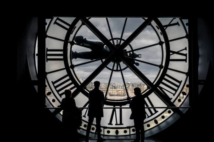 Three people in silhouette stand and look out of the famous clock window at the Musee d'Orsay. Through the window we see the line of Haussmannian buildings across the Seine and to the extreme left a bit of the Sacre Coeur in the distance. Mostly we see a partly cloudy sky. The people and interior are in shadow.