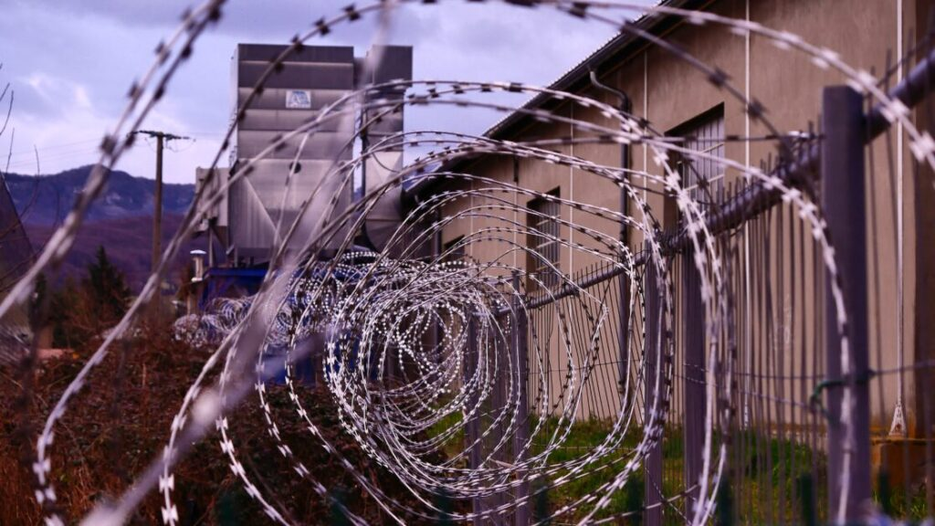 A spiral of barbed wire with a low building and a mountain around it. It seems to be a prison gate.