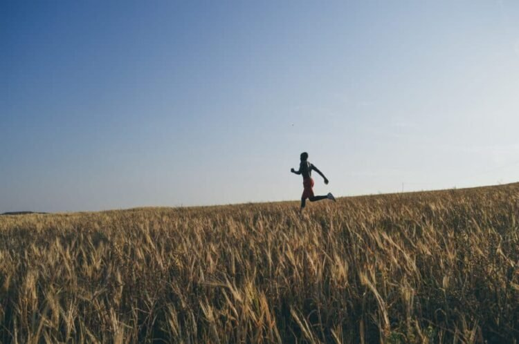 A man runs in a field of tall grass or wheat. We see him in the middle ground,the wheat is all around us and at eye level nearly in the foreground.