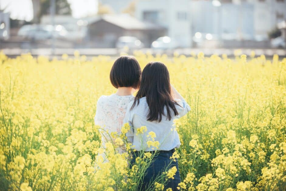Two little girls stand in a field of yellow flowers and look towards what seems to be cityscape that is blurred in the background. One girl has chin-length black hair and the other has black hair below the shoulders.
