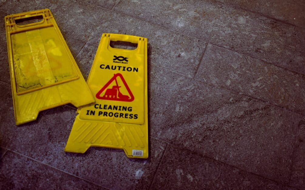 """A """"wet floor"""" sign, marked """"Caution Cleaning in Progress"""" has broken in half and is lying on the stone floor, which is hopefully dry now."""