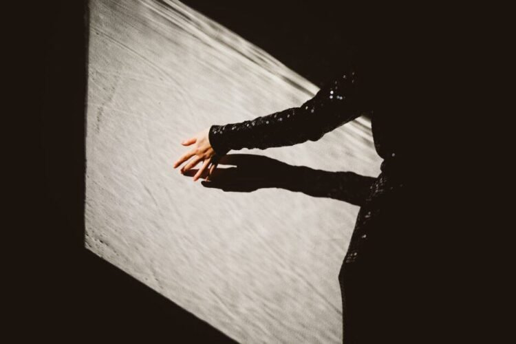 In a patch of light, probably the projection of a sunny window onto a gray wall, a woman runs her hand along the wall. The rest of the scene is in darkness. We can make out part of her back and her sleeve. She is wearing a black sequined long-sleeved top.