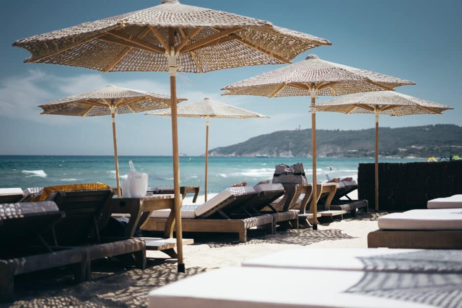 Plush beach lounge chairs and classy woven bamboo or straw beach umbrellas on a beach in Saint-Tropez. In the background we can see the ocean and the hilly coastline.
