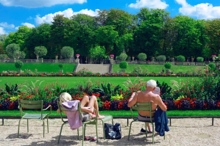 An old man and a young woman engage in what is one of most Parisians' favorite pastimes: sunbathing in a public park. The park in question is the classy Jardin du Luxembourg, but since all rules of decorum go out the window when it comes to catching some rays, the man has his shirt and shoes off as he reads a newspaper in one of the Jardin's famous green-painted metal chairs. The young woman beside him also has her shoes off. She is slouching in one chair and using another to put her feet on. We see them from behind. In the background are the verdant lawns lined with colorful flowers that the Jardin is known for.