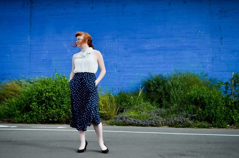 A red-haired woman stands in front of a bright blue wall with verdant green bushes below it. Her face is turned to the side and we see her full body, dressed in a white sleeveless top with black polka dots, a high collar bow. Her calf-length skirt is dark blue with white dots. She wears black shoes that match her black glasses.