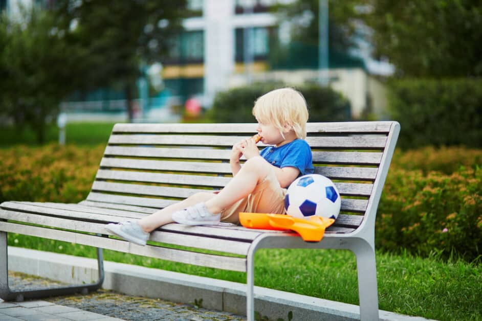 A little boy with blonde hair, shorts, sneakers, and a t-shirt sits on a bench outside and contemplatively stares off while eating a snack