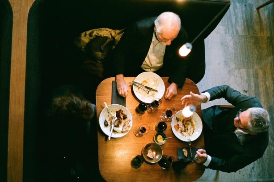 Overhead view of two old men and a younger person at a booth in a cafe. The man on the right has put down his silverware leaning on his plate, so that he can talk with his hands. The man in the center has finished his food and placed his fork and knife on his plate, parallel to each other, about the three or four o'clock position. The younger man, on the left, has placed his fork and knife facing each other and forming a triangle in the middle of his plate, indicating that he's taking a break.