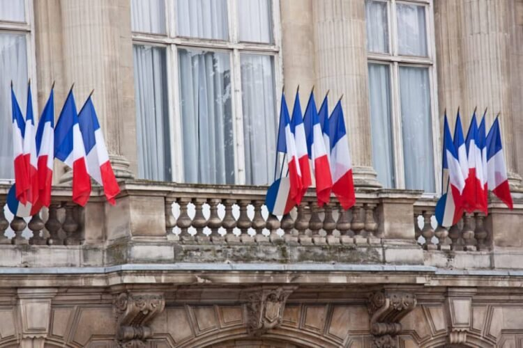 Groups of five French flags on flagpoles on the balconies of an official-looking building
