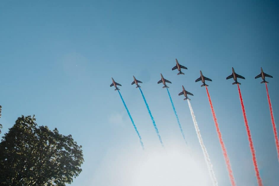 A group of 8 fighter jets fly across a blue sky. Behind each jet is a trail of colored smoke, first blue coming from the first three, then white from one in the center, and then red from the last three - blue, white, and red, the colors of the French flag.