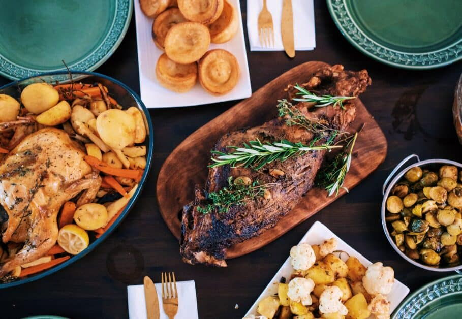 An overhead shot of a set table. The focus is on the courses, which include a seasoned meat with herbs, mushrooms, cauliflower, and chicken with potatoes and carrots.